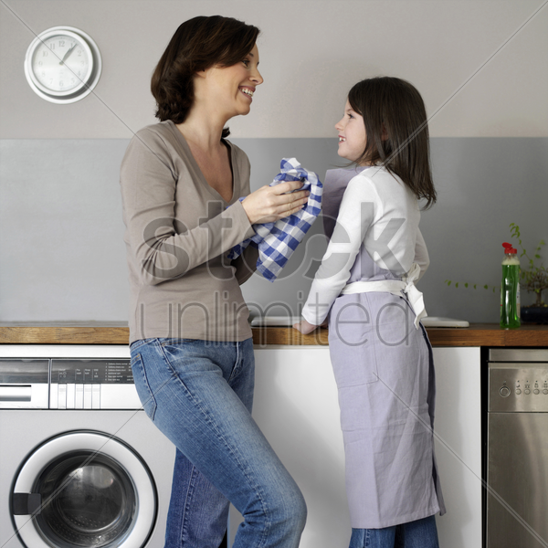 mother and daughter washing the dishes together stock photo