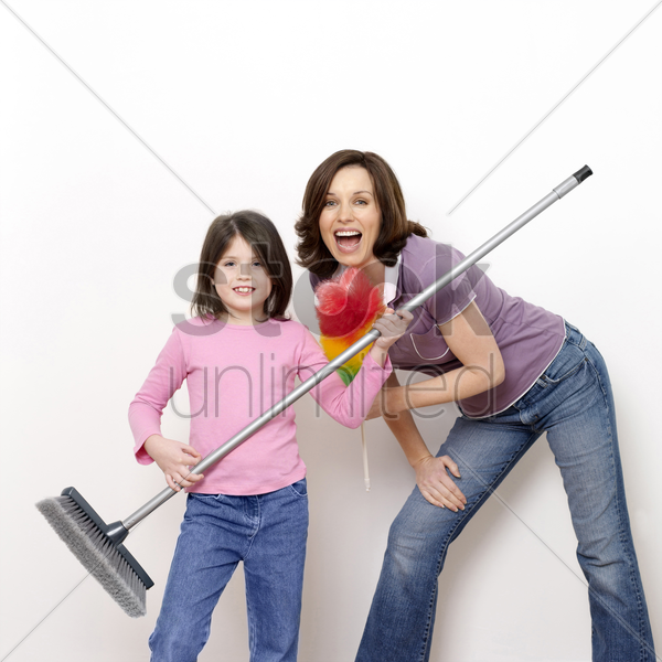 mother and daughter with broom and feather duster stock photo