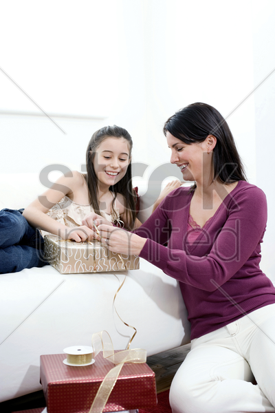 mother and daughter wrapping present stock photo
