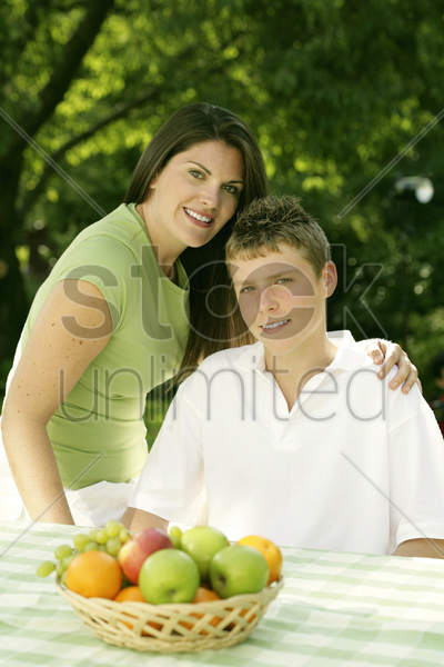 mother and son posing at the picnic table stock photo