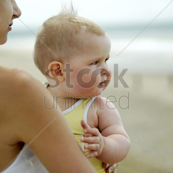 mother carrying baby girl stock photo