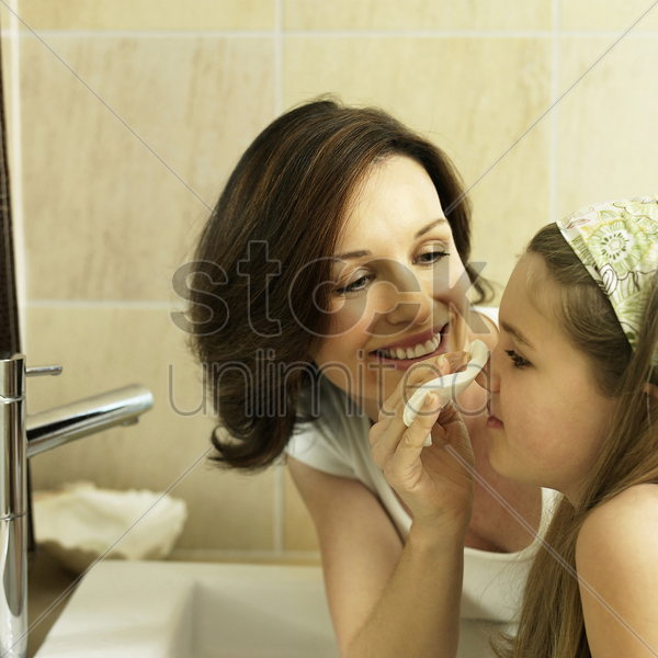 mother cleaning her daughter's face with a facial cotton stock photo