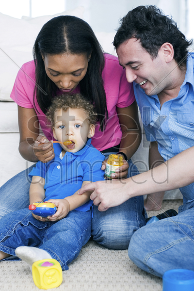 mother feeding son with father watching stock photo