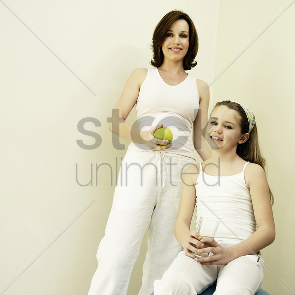 mother holding a green apple while daughter holding a glass of water stock photo