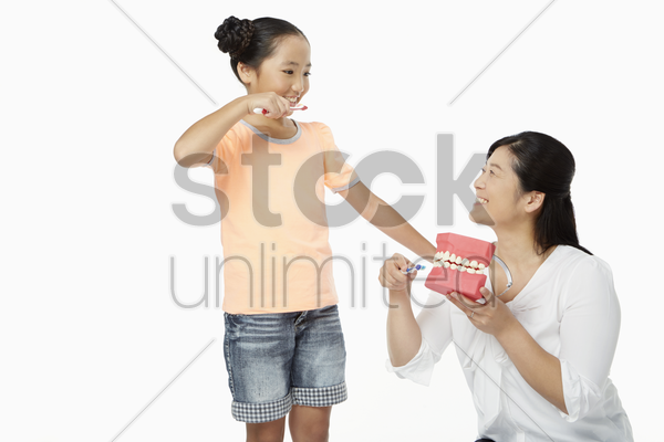 mother teaching daughter how to brush teeth stock photo