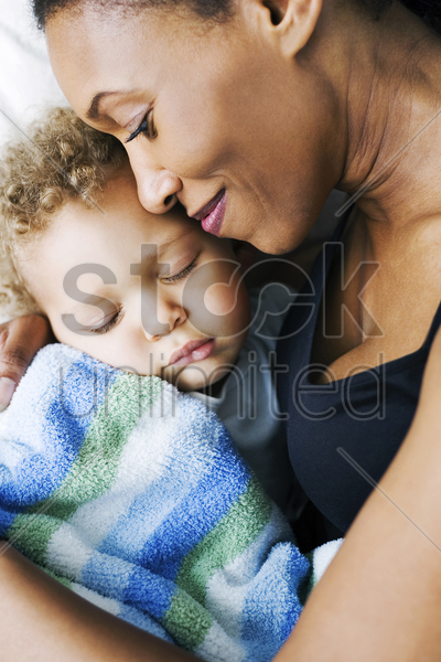 mother watching son sleeping stock photo