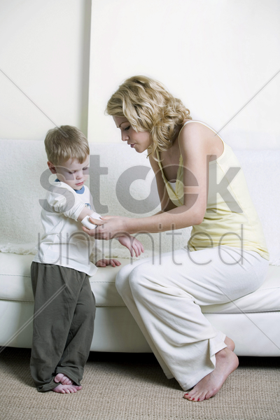 mother wrapping son's arm with bandage stock photo