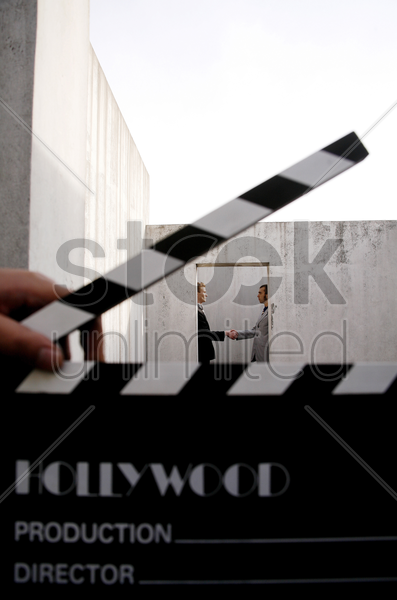 movie director holding clapboard with businessmen shaking hands in the background stock photo