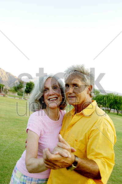 old couple dancing in the park stock photo