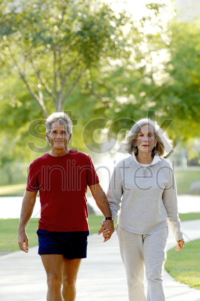 old couple holding hands while walking in the park stock photo