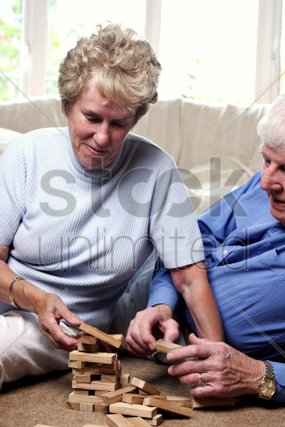 old couple playing with building blocks stock photo