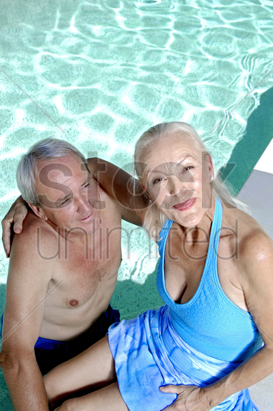 old couple relaxing by the pool side stock photo