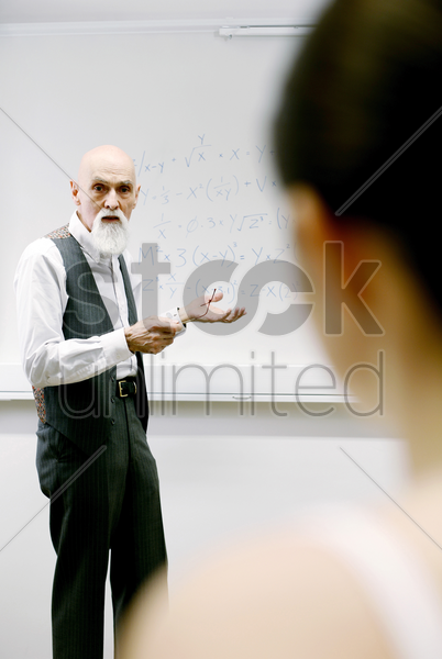 old professor explaining new formula to his students stock photo