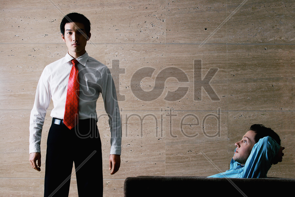 one businessman standing while the other one relaxing on the couch stock photo