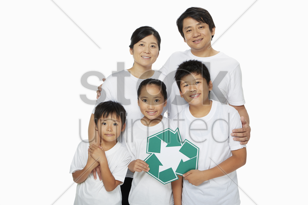 one happy family holding up a recycle logo stock photo