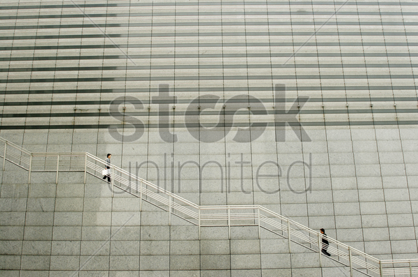 one man going up while the other going down the stairs stock photo