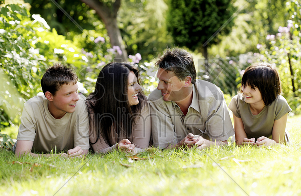 parents and children lying forward on the grass stock photo