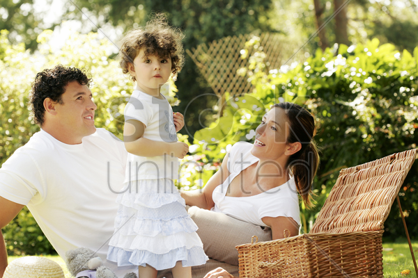 parents and daughter picnicking in the park stock photo