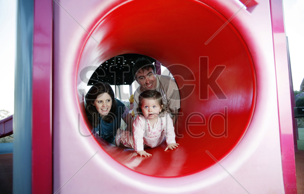 parents and daughter playing in the playground stock photo