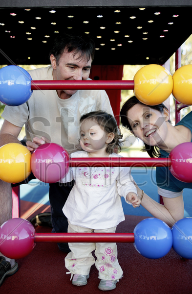 parents and daughter playing with abacus in the playground stock photo