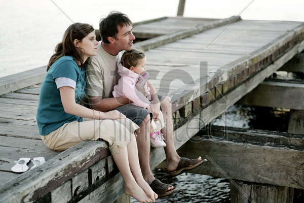 parents and daughter sitting at the pier stock photo