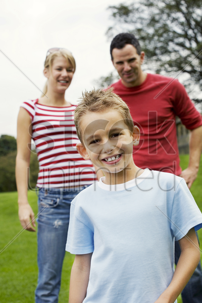 parents and son having fun in the park stock photo