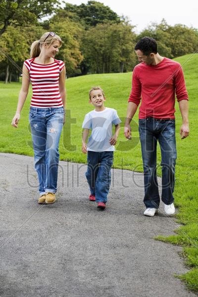 parents and son walking in the park stock photo