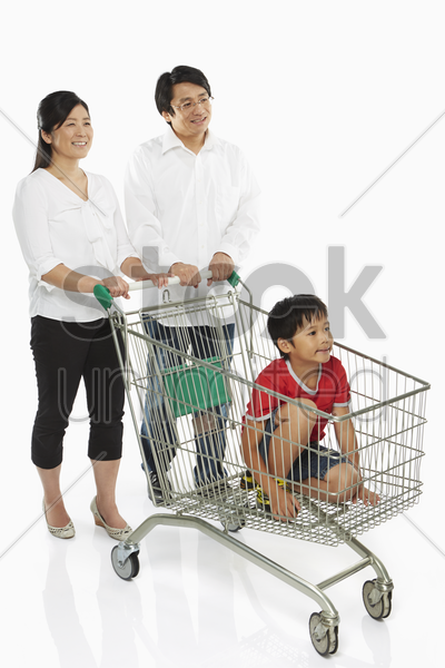 parents pushing a shopping cart with son in tow stock photo