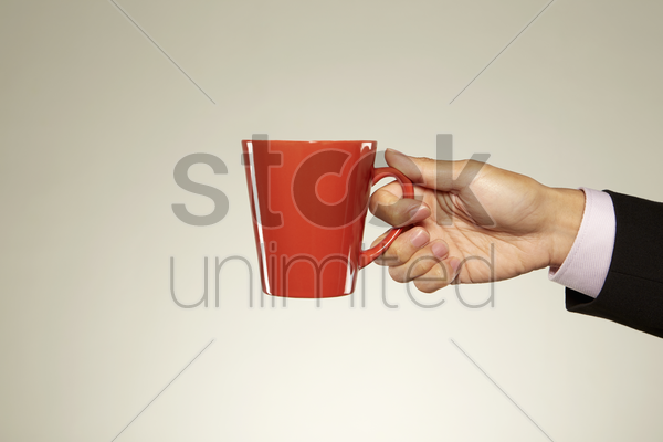 person holding up a red mug stock photo