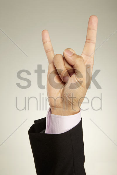 person showing horn sign stock photo