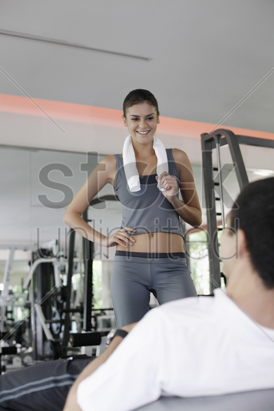 personal trainer helping man exercising in gymnasium stock photo