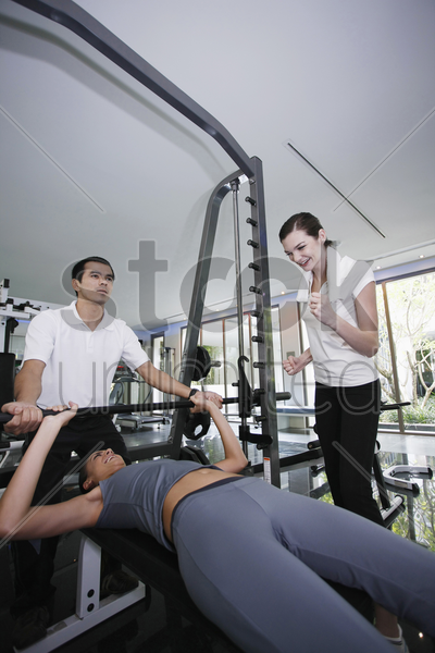 personal trainer helping woman exercising in gymnasium, friend giving support stock photo