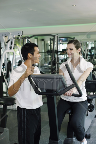 personal trainer helping woman exercising in gymnasium stock photo