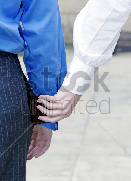 pickpocket stealing from a businessman stock photo