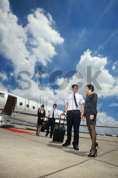 pilots and flight attendants walking away from private jet stock photo