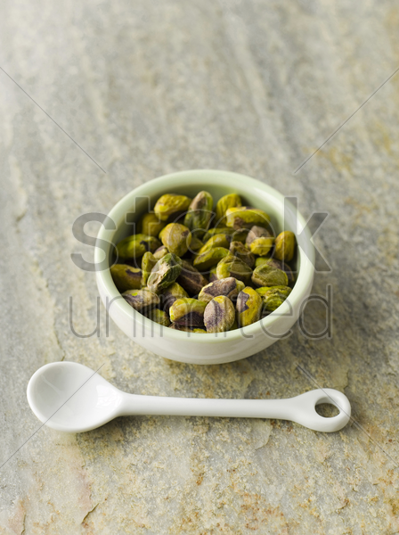 pistachios in green bowl with white spoon stock photo