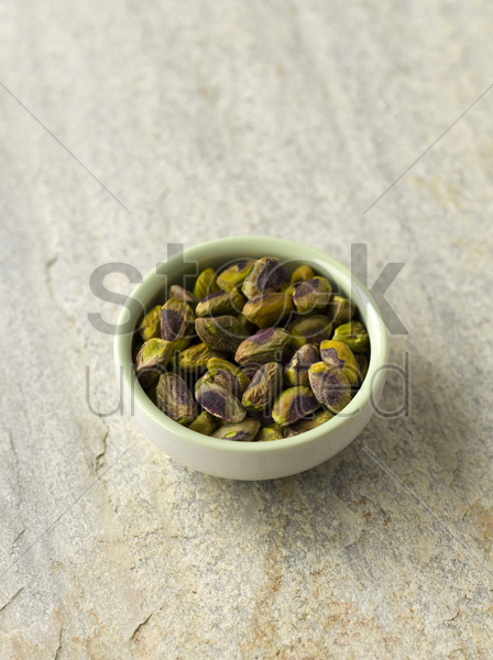 pistachios in green bowl stock photo