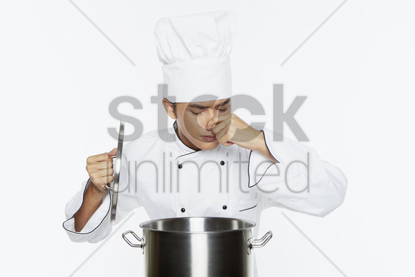 portrait of a male chef smelling food from the pot stock photo
