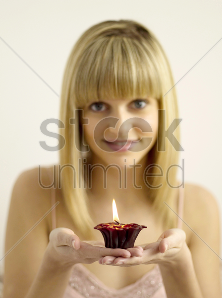 pretty girl holding a lighted aromatherapy candle stock photo
