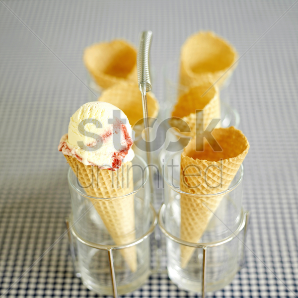 raspberry ripple ice cream cone in holder on table with blue gingham cloth stock photo