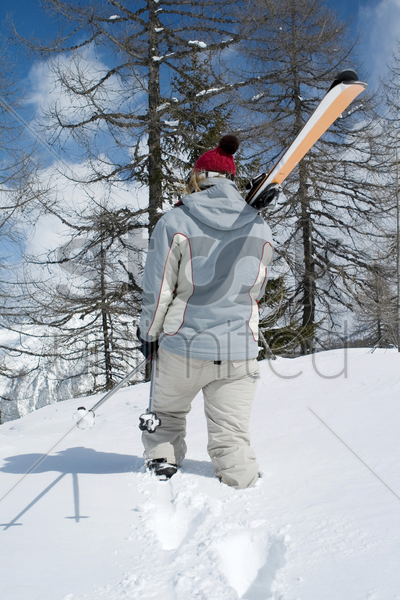 rear view of a man holding snowboard walking away from camera stock photo