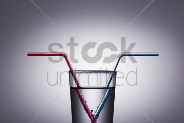 red and blue drinking straw in a glass of water stock photo