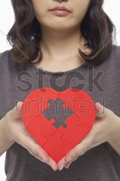 sad woman holding up a red heart shape with a missing puzzle piece stock photo