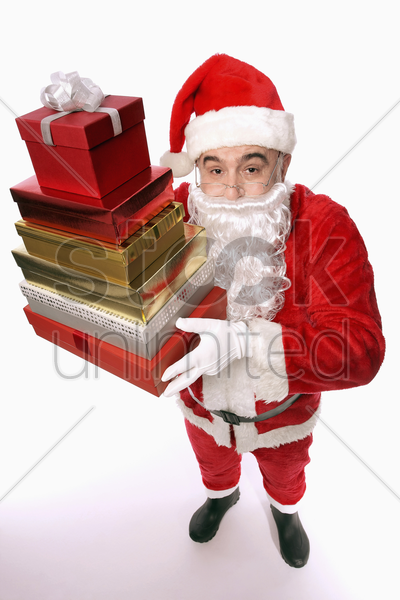 santa claus holding a stack of presents stock photo