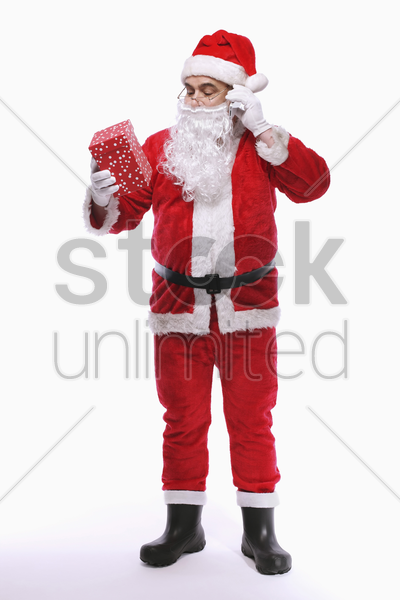 santa claus looking at present while talking on the mobile phone stock photo