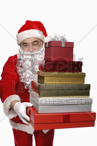 santa claus with a stack of presents stock photo