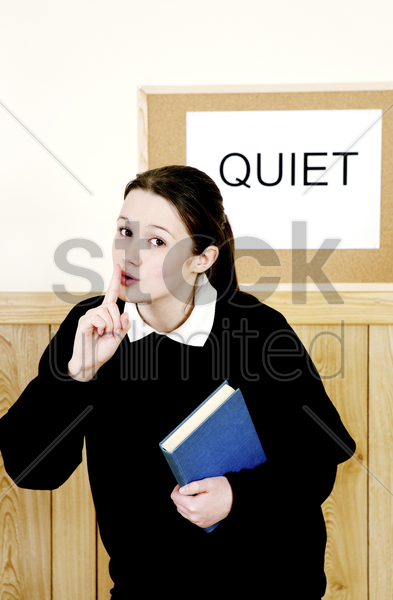 school girl showing a hushing sign stock photo