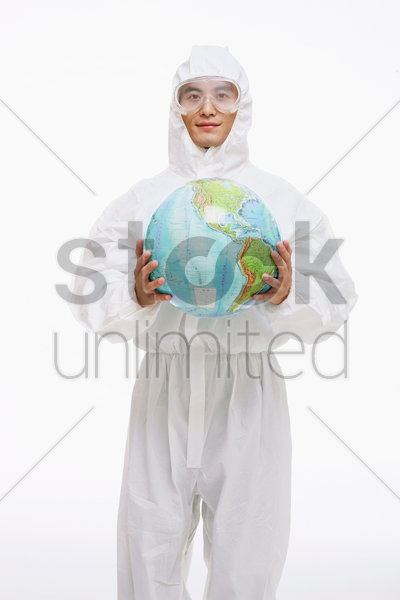 scientist in protective suit holding globe stock photo