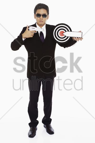 security staff pointing a gun to a dart board stock photo