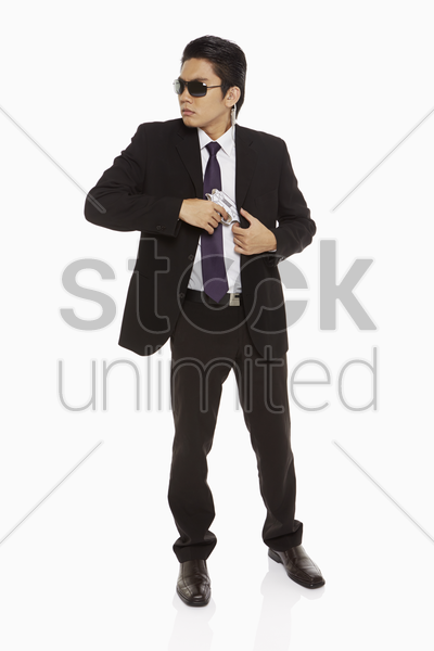 security staff taking out a gun from his jacket stock photo